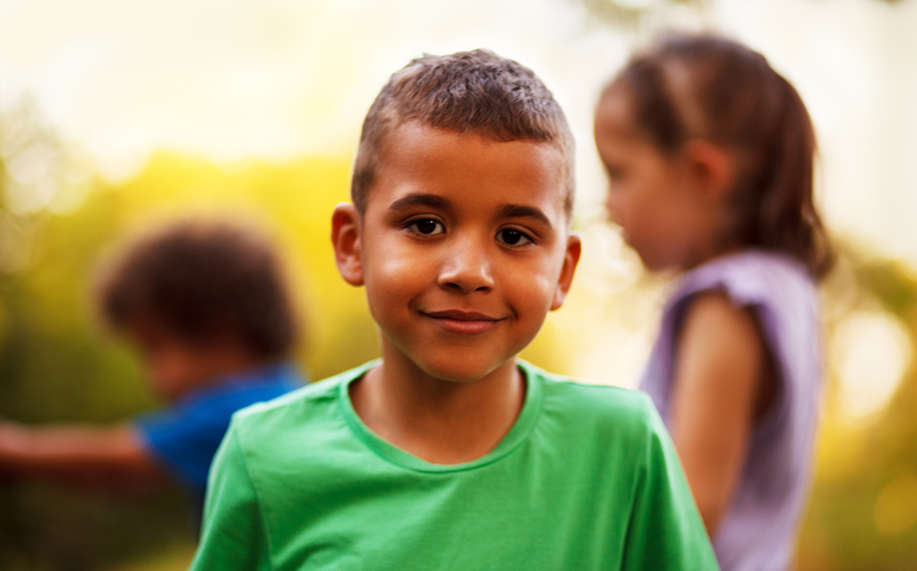 A young boy smiles at the camera