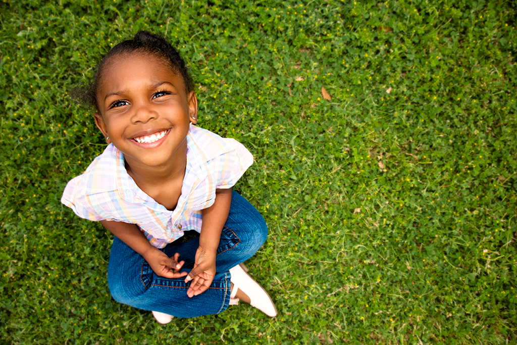 A young African-American girl is sitting in the grass, smiling.