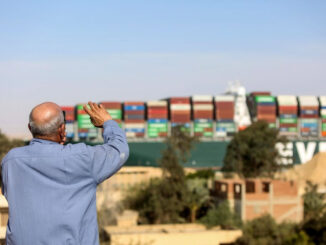 A spectator waves as the Ever Given container ship moves along the Suez Canal towards Ismailia after being freed -energynewsbeat.com