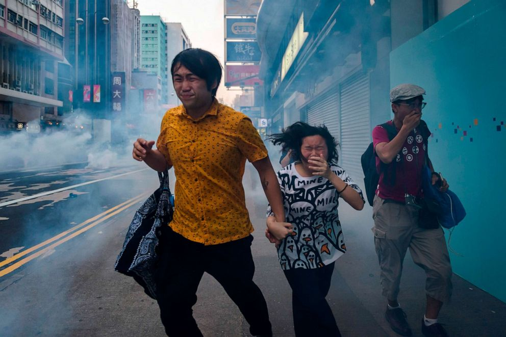 PHOTO: Bystanders along Nathan Road react from tear gas fired by police during a pro-democracy march in the Kowloon district in Hong Kong, Oct. 20, 2019.