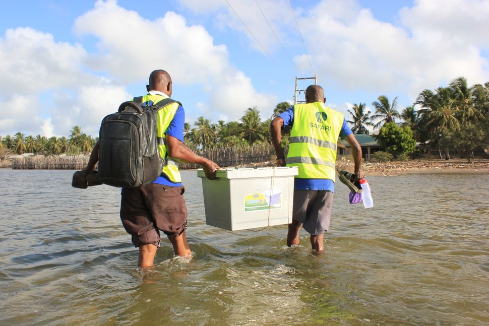 Safari Doctors carry supplies ashore at one of the stops on their route. The group sets up mobile clinics in each village for