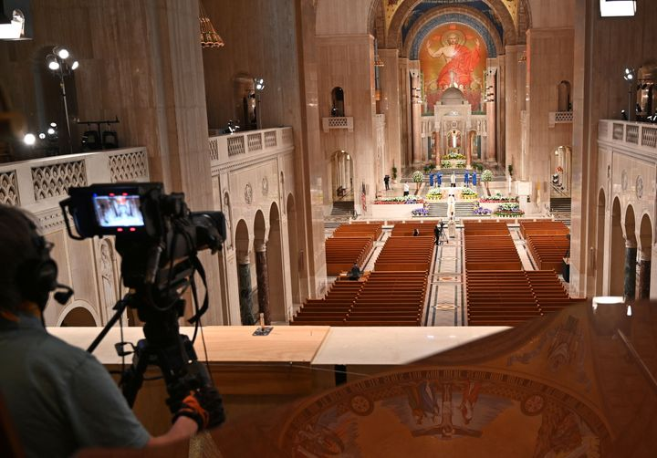 A cameraman films members of the clergy arriving for an online Easter Sunday Mass in front of empty pews at the Basilica of t