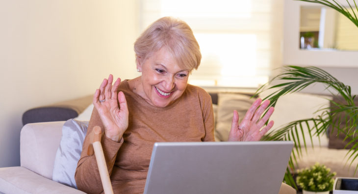 Happy mature woman waving to someone while having a video call over laptop at home. Gray-haired senior woman waving hand in front of laptop while having video call with her family members.