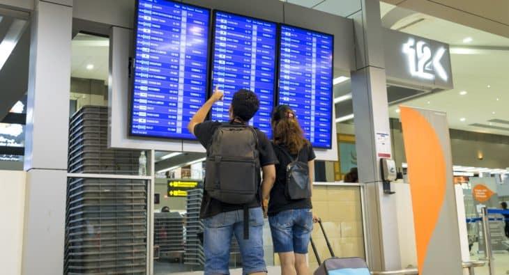 Traveler looking flight information screen board in airpor