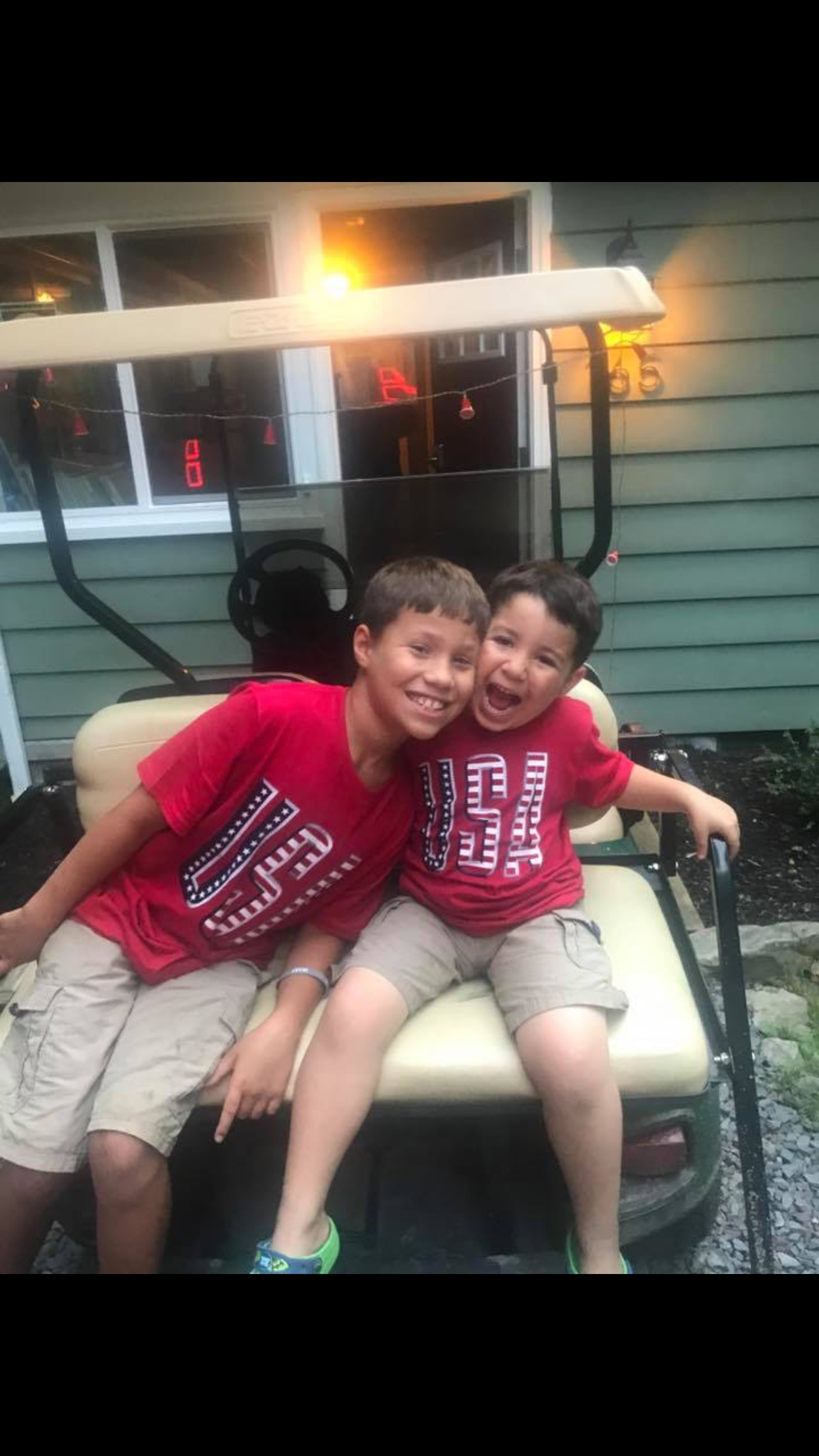Two children smiling on back of golf cart