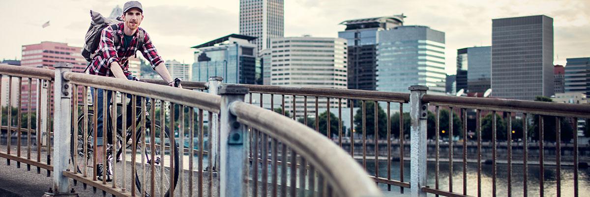 man on bicycle crossing bridge