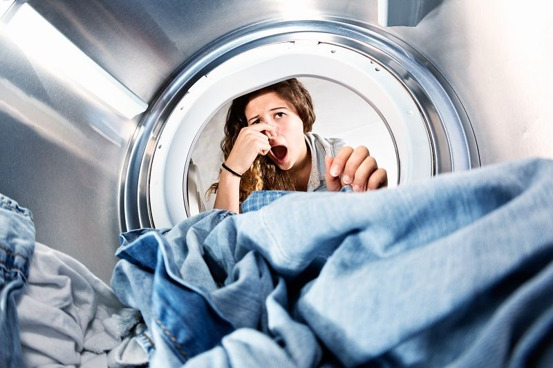 Laundry-left-in-clothes-dryer-stinks!-Unhappy-woman-holds-nose.-cm