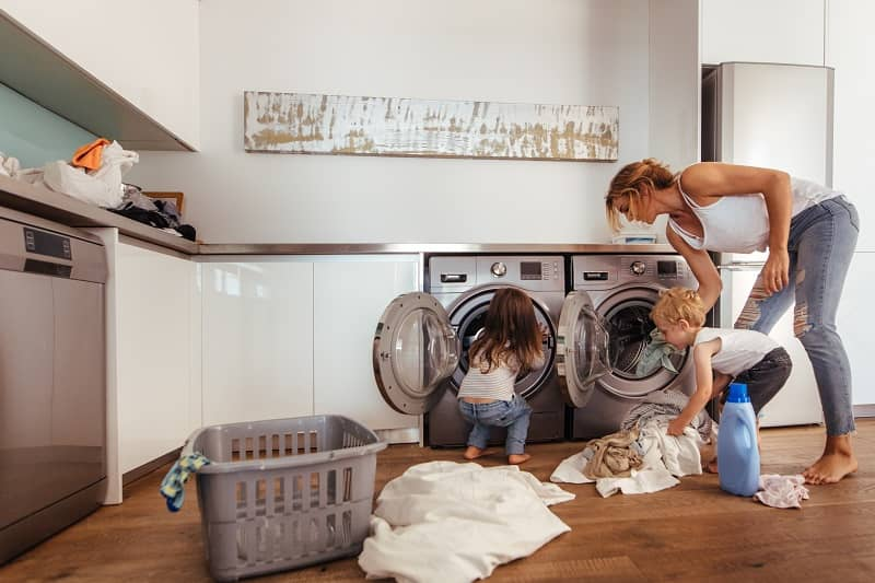 Family doing laundry together at home-cm