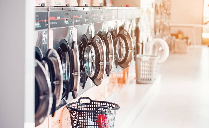 Row of industrial laundry machines in laundromat in a public laundromat, with laundry in a basket-cm