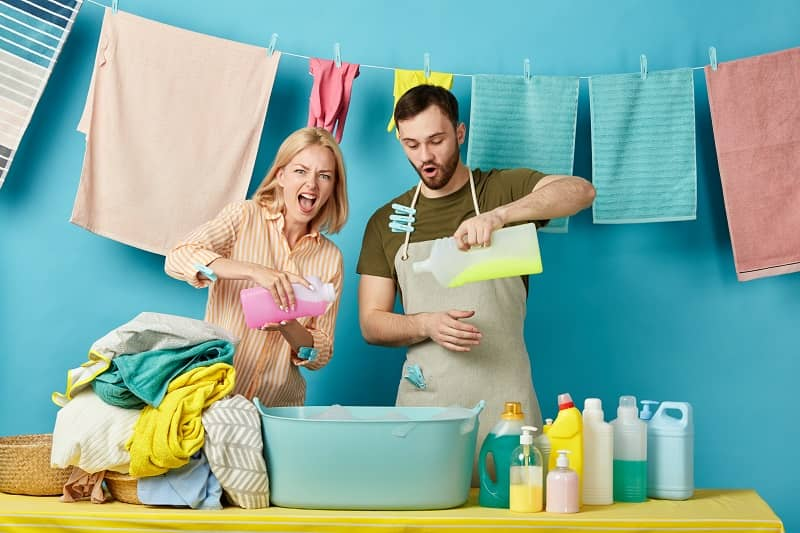 crazy funny couple pouring different detergents in the bowl-cm