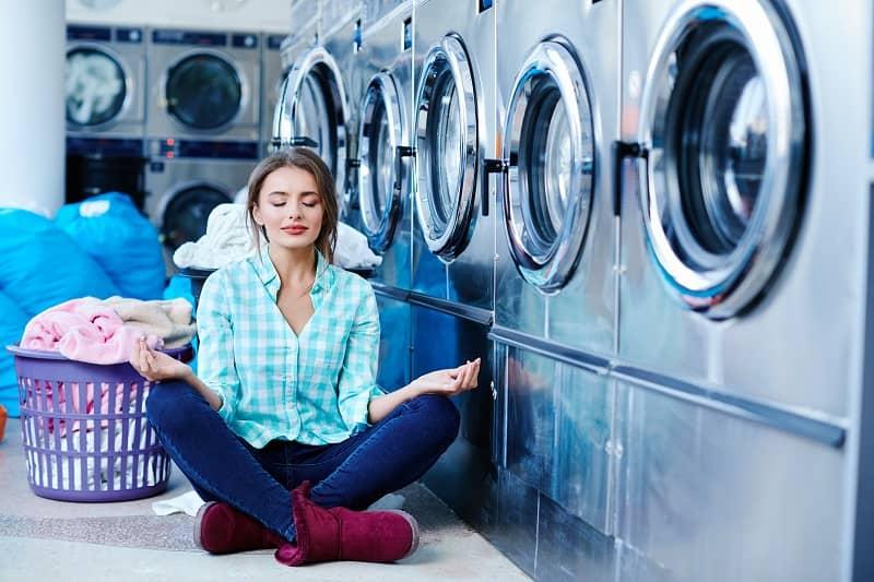 Woman meditating near washing machines-cm