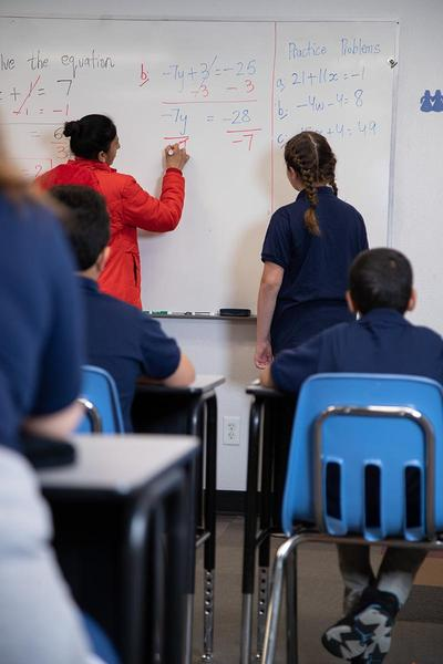 Classroom - T&S Doing math at the board.27f01fecdc6b6fb0850c2e826004c787