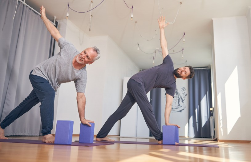smiling barefoot men performing a yoga exercise