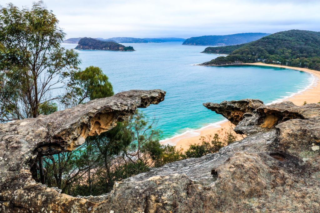 Broken Bay ocean and beach through rocky outcrop