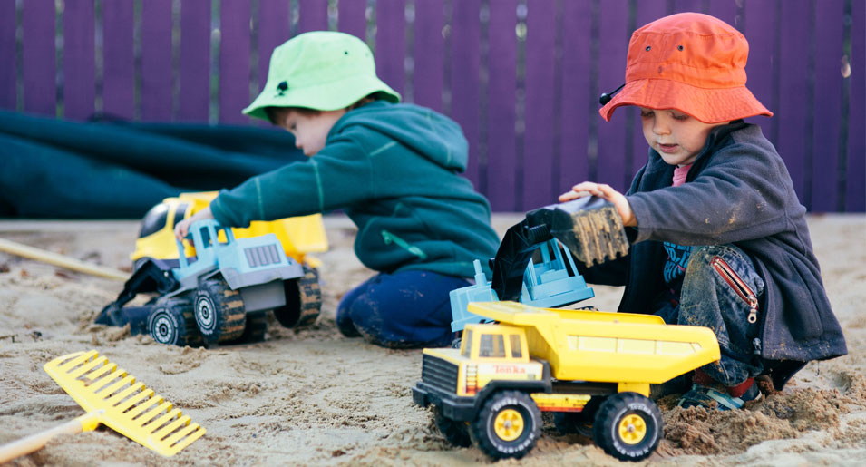 Children playing with trucks in sand