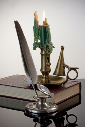 Antique inkwell and quill pen with a brass candlestick and red book - white vignette background