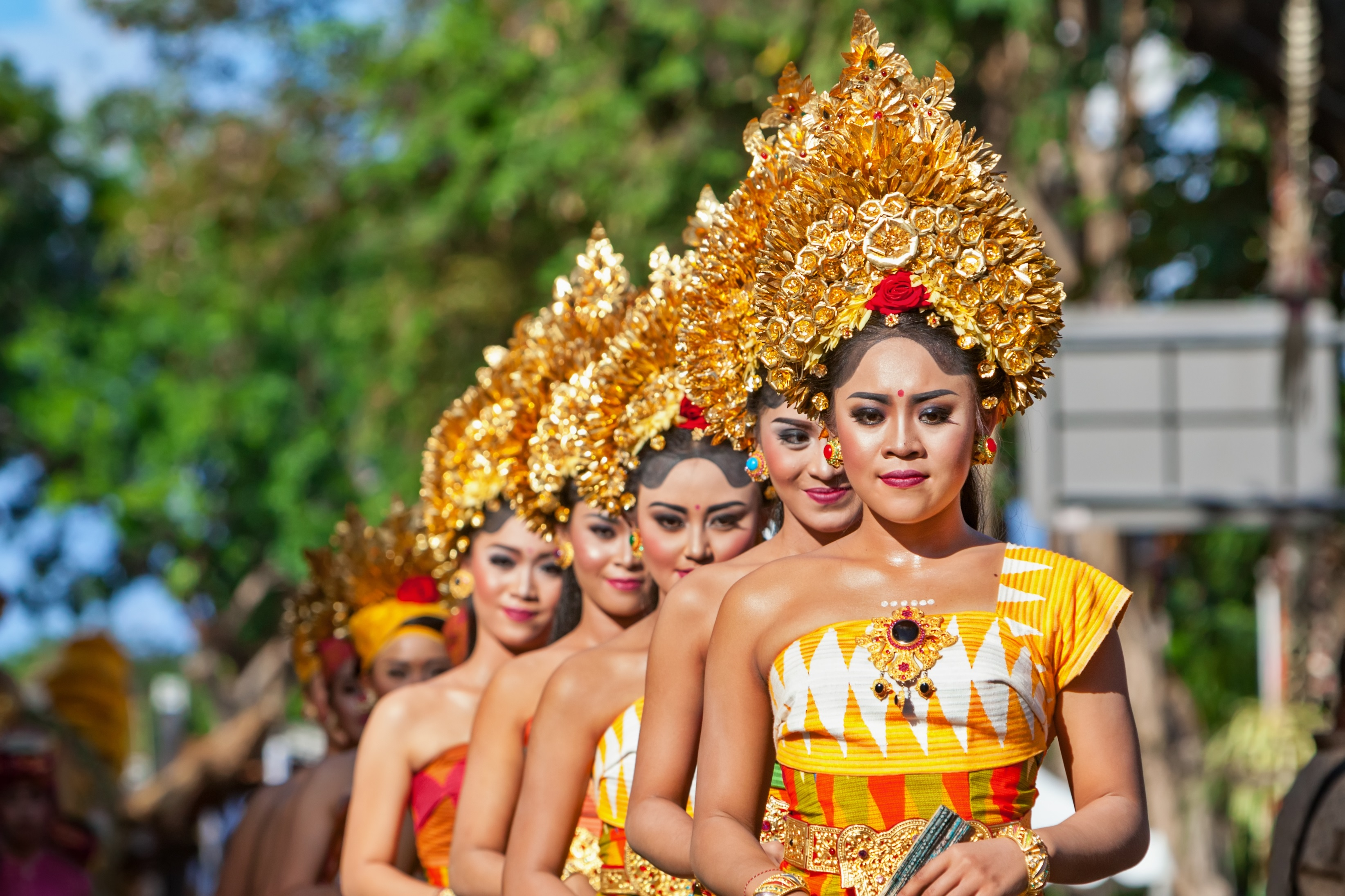 Denpasar, Bali Island, Indonesia - June 11, 2016: Group of Balinese people. Beautiful dancer women in traditional costumes dance on street parade at art and culture festival.
