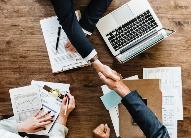 birds eye view of business people shaking hands over folders and laptop on wooden desk