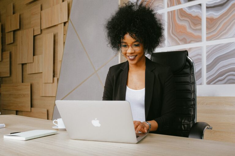 black woman smiling and working on her apple laptop.