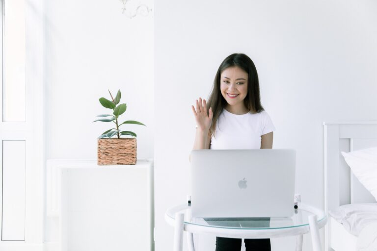 a woman wearing a white shirt smiling and waving into the computer camera.