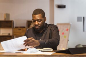 A black man wearing a black long sleeved shirt looking and reviewing papers.