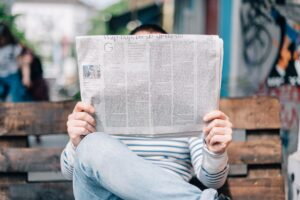 man holding newspaper looking at media and ads.