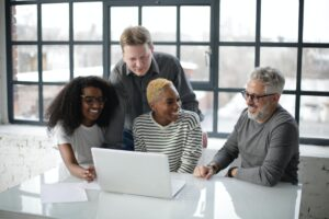A marketing team sitting around a laptop working on brand strategy.