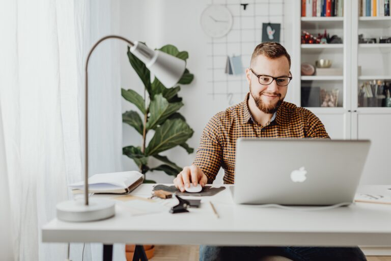 man in a brown button up shirt sitting at his desk on his macbook smiling.
