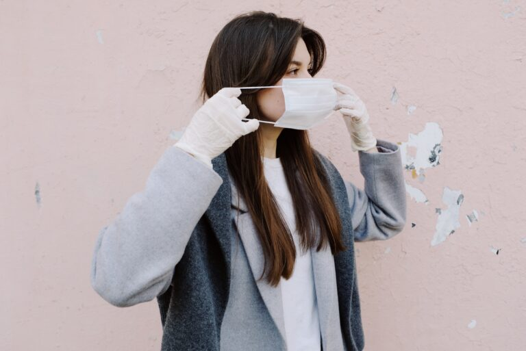 woman with long brown hair putting on a mask with gloves in front of a pink wall