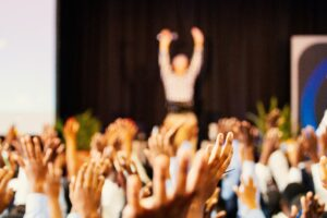 people raising their hands at a group conference