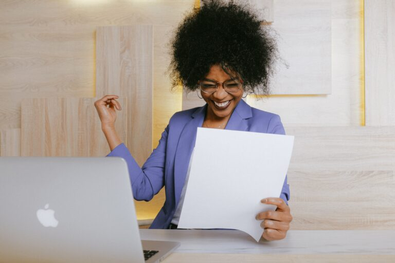 a woman excited looking at a piece of paper.