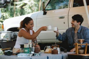 a picture of a woman and a man camping and drinking tea