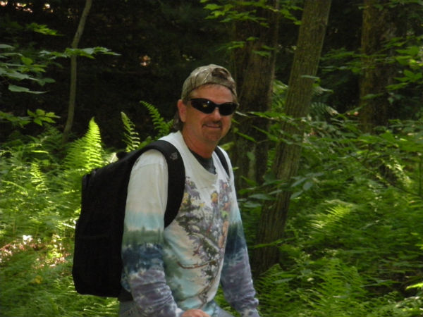 man hiking in woods with backpack