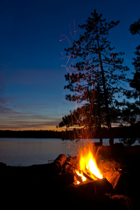 roaring campfire at night alongside a lake