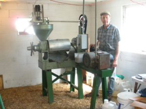 man standing with machine and auger for feeding wood chips to make alternative fuel