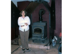 woman standing in front of custom wood stove frame