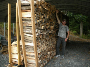 man reaching with arm alongside large stacked firewood pile
