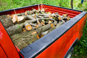 firewood piled in back of red pickup truck