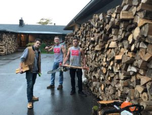 3 men with woodcutting tools next to stack of firewood