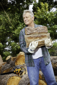 elderly man carrying firewood in his arms