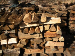 Piles of  firewood stacked on wooden pallets using the cribbing method
