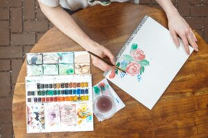hands on table painting flowers in watercolors