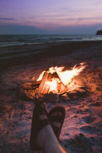 feet with sandals by a roaring wood fire on beach