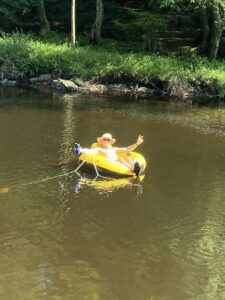 man with hat and sunglasses relaxing in yellow inner tube in middle of mountain stream