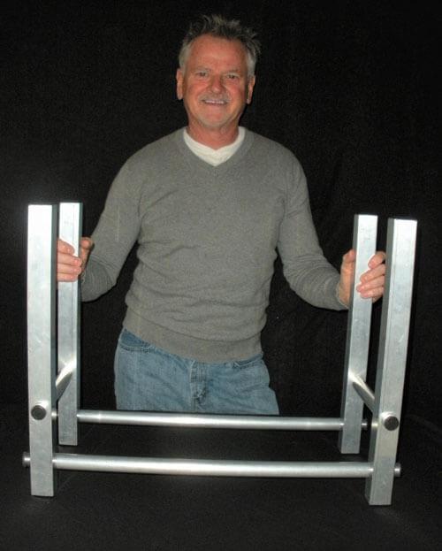 man standing holding onto aluminum firewood holder frame