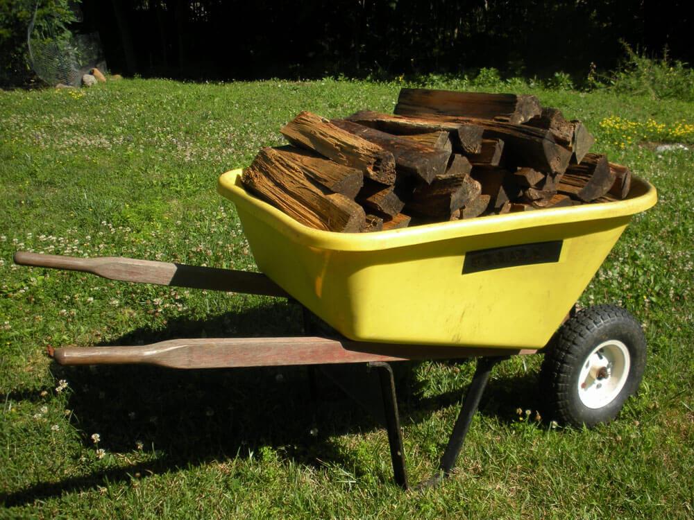 yellow wheel barrow filled with split firewood