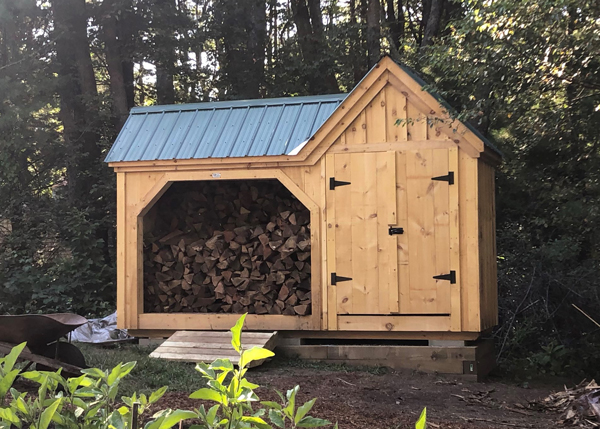wooden firewood holder house with green metal roof and pull open doors
