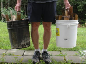 man in shorts holding (2) 5 gallon buckets with wood