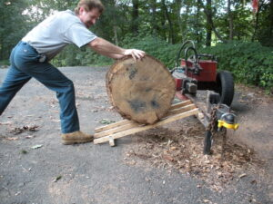 man rolling large tree trunk up a wooden ramp onto a custom log splitter