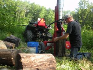 Man kneeling in field splitting large logs with a vertical hydraulic log splitter